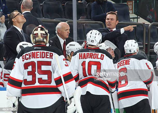 Interim coach Lou Lamoriello and cocoaches Adam Oates and Scott Stevens of the New Jersey Devils talk to their players during a timeout in the third...