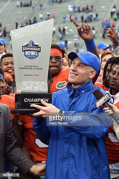 Interim head coach DJ Durkin of the Florida Gators lifts the trophy following a victory over the East Carolina Pirates in the Birmingham Bowl at...