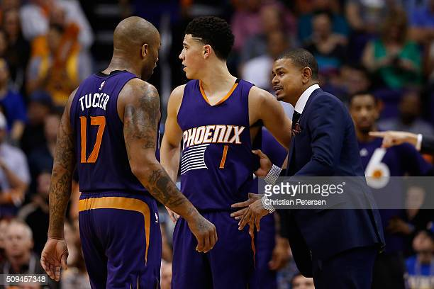 Interim head coach Earl Watson of the Phoenix Suns talks with PJ Tucker and Devin Booker during the second half of the NBA game against the Golden...