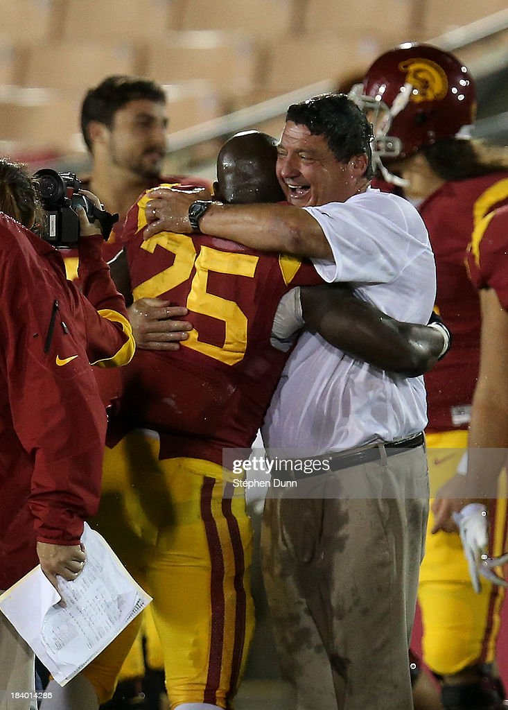 Interim head coach Ed Orgeron and running back Silas Redd #25 of the USC Trojans embrace at the end of the game with the Arizona Wildcats at Los Angeles Coliseum on October 10, 2013 in Los Angeles, California. USC won 38-31.