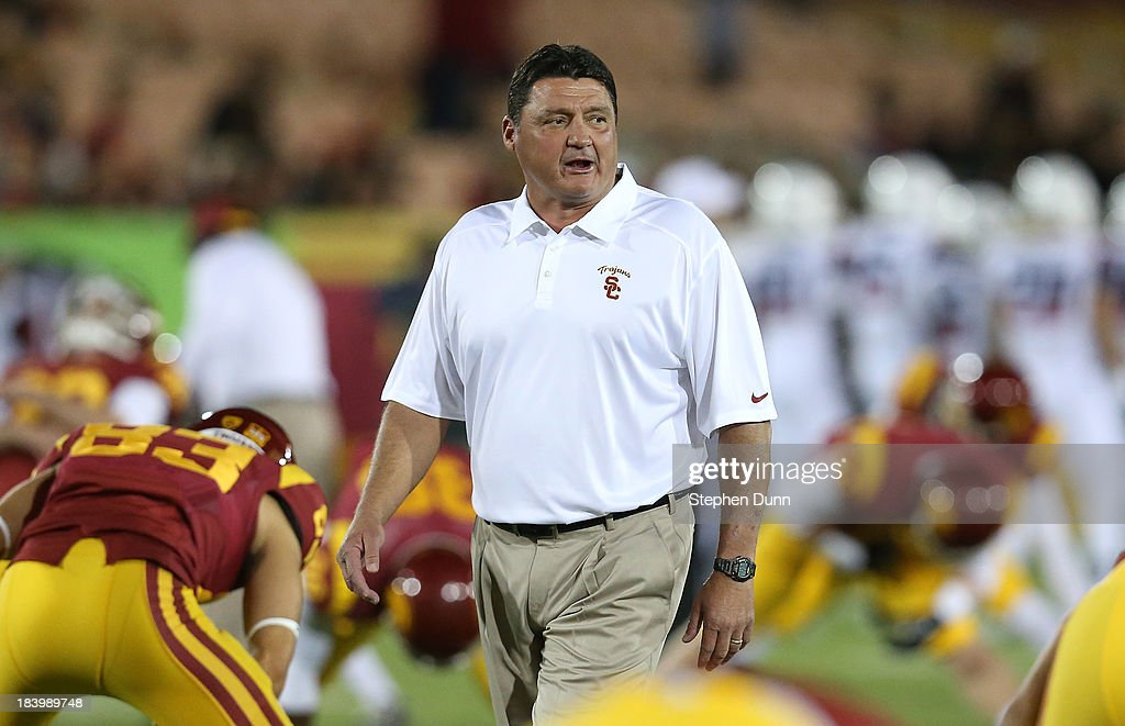 Interim head coach Ed Orgeron of the USC Trojans leads his team as they warm up for the game against the Arizona Wildcats at Los Angeles Coliseum on October 10, 2013 in Los Angeles, California.