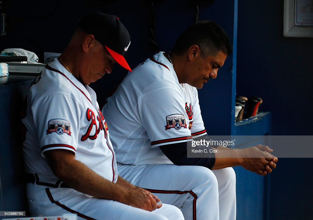 Interim manager Brian Snitker #43 and first base coach Eddie Perez #12 look on during the fourth inning against the New York Mets at Turner Field on June 24, 2016 in Atlanta, Georgia.