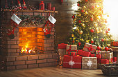 interior christmas. magic glowing tree, fireplace and gifts