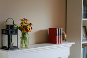 Photo of flowers in a vase next to a lantern on top of a mantle indoors