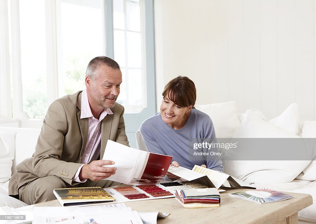 Interior designer showing samples to customer : Stock Photo