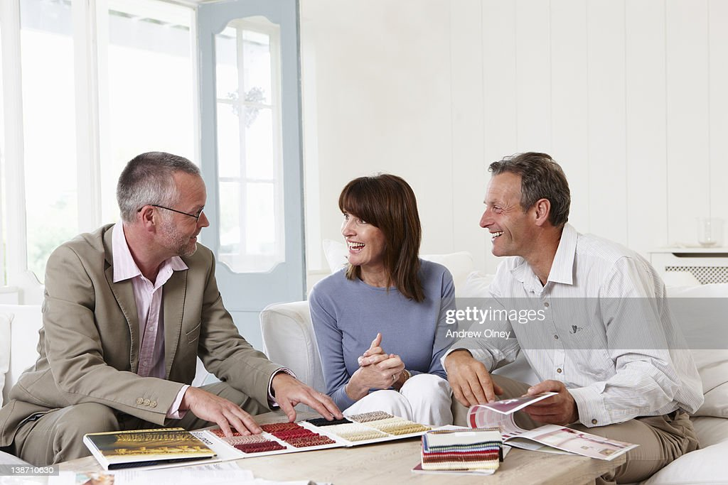 Interior designer showing samples to customers : Stock Photo