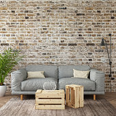 Modern gray sofa with  pillows in front of an empty brick wall. Square composition. interior template. designer copy space render with blank picture poster frame copy space. wooden coffee table, large