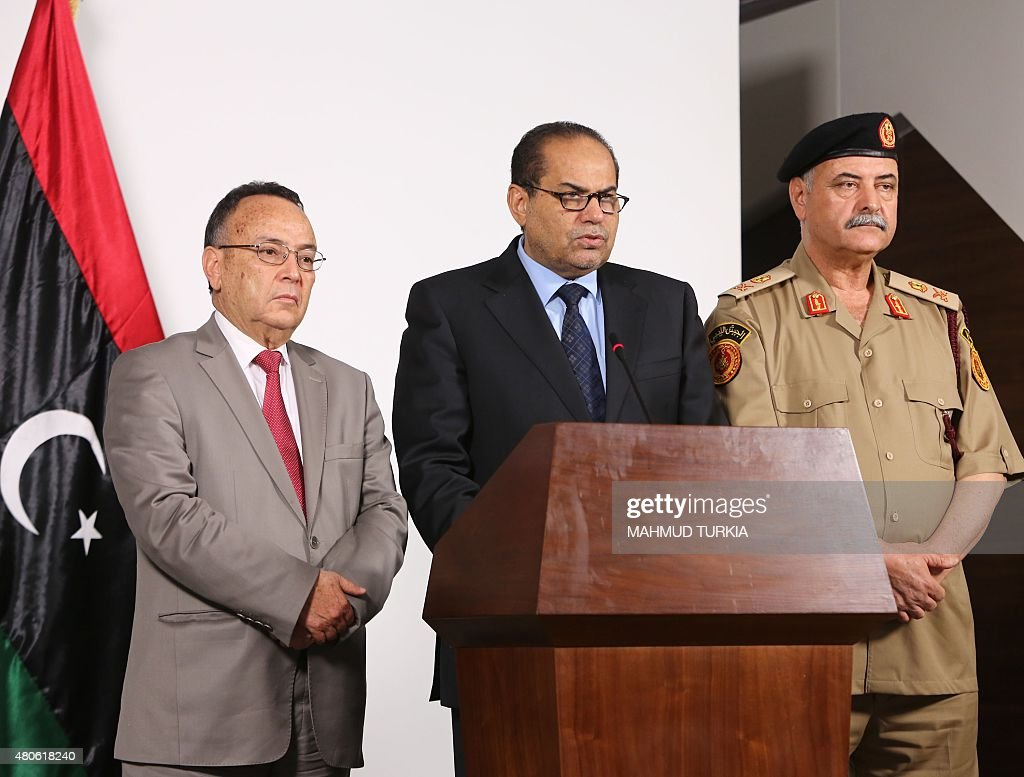 Interior Minister of the National Salvation Government, Mohammed Sheater (C), speaks to the press as Minister of Foreign Affairs for the National Salvation Government, Mohamed El-Ghirani (L), looks on as they discuss a border wall being built by Tunisia on the Libyan border, in Tripoli on July 13, 2015. Tunisia's Prime Minister Habib Essid announced plans to build a wall, 160 kilometers from the coast inland, along part of its eastern border with Libya in a bid to contain the crossing of militants.