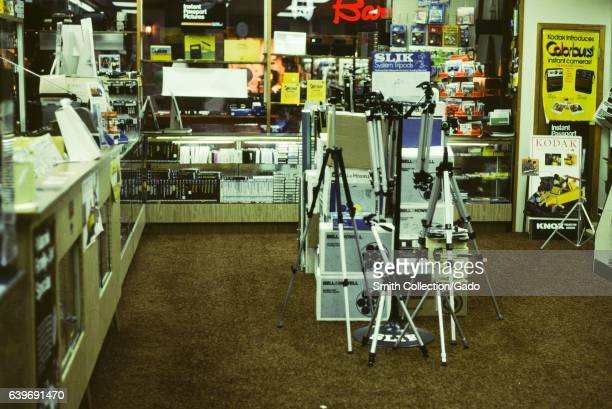 Interior of a camera store with tripods and other equipment 1975