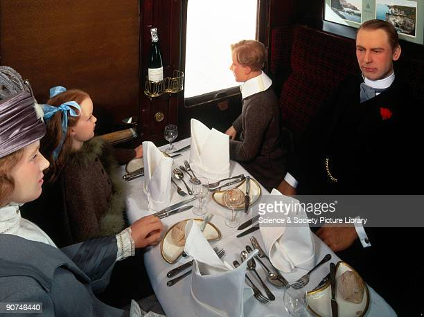 Interior of a dining car with mannequins represnting a family seated at a table set for dinner This dining car was built jointly for the Midland...
