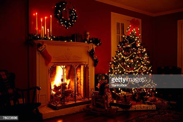 Interior of a lighted Christmas tree near a lit fireplace.