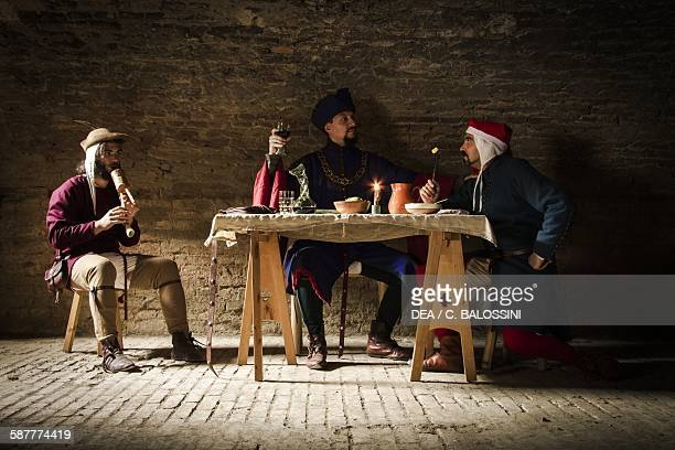 Interior of a tavern with musician and diners 15th century Historical reenactment