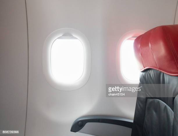 Interior of airplane with passengers seats waiting to taik off on the window.