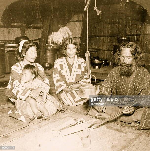 Interior of an Ainu home showing owner and family Yezo Japan