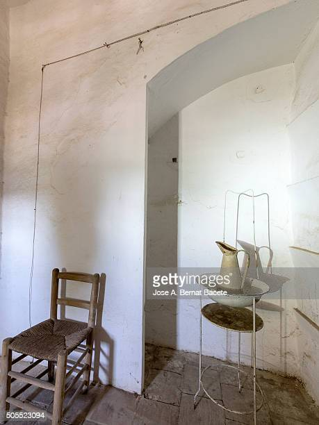 Interior of an ancient room with a chair of wood and a palancana