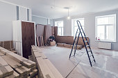 Interior of apartment  during construction, remodeling, renovation, extension, restoration and reconstruction - ladder and construction materials in the room.