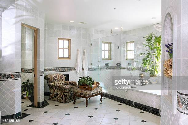 Interior of domestic bathroom with armchair and stool