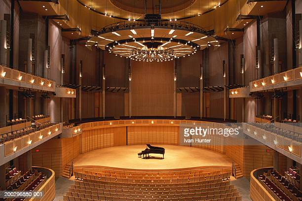 Interior of empty theater, piano at center stage, elevated view
