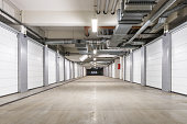 An underground parking structure sits empty, its beige floor stretching out toward a dark exit ahead.  On either side are long rows of closed storage bays with white doors.  The bays are numbered.  Th