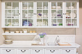 Interior of white domestic kitchen with full size cupboard on the wall.