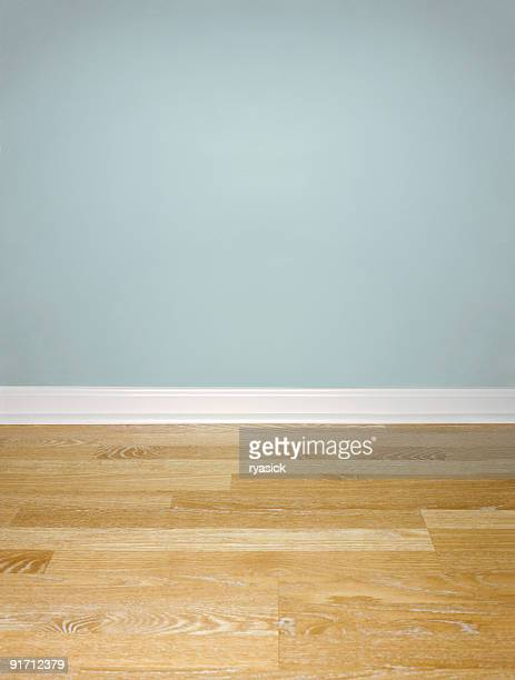 Interior of Wood Floor with White Baseboard and Blue Wall
