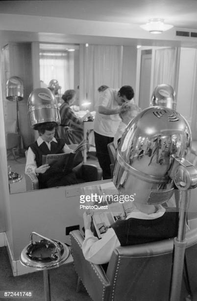 Interior view of a beauty salon reflected in the shop's mirror Washington DC November 20 1957 As a woman sit under a dryer a male hairstyist cuts...