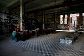 Interior view of an abandoned industrial building with graffiti on the walls