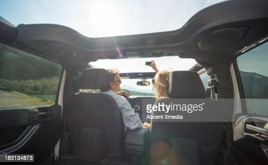Interior view of couple driving jeep, mtn road