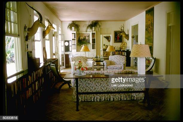 Interior view of Ernest Hemingway's home in outskirts of Havana showing comfortable living room seating area and prominent display of stuffed animal...