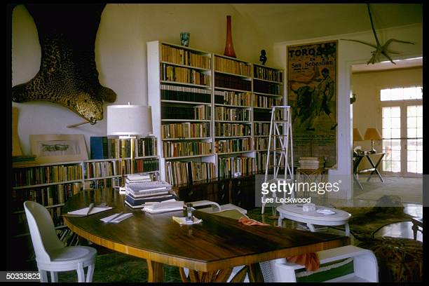 Interior view of room in Ernest Hemingway's home on the outskirts of Havana showing books bullfighting poster and animal skins w stuffed heads on...