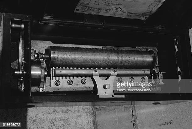 Interior view of the mechanism of a large music box showing metal cylinder with pins encoding melody of an unknown song with steel comb used to pluck...