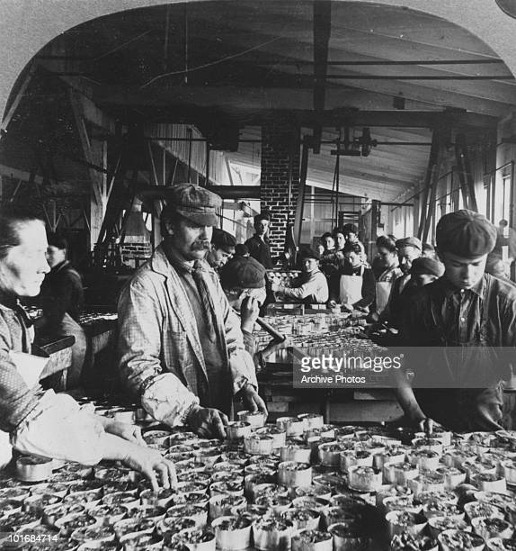 Interior view of the production line at a salmon canning establishment in Astoria Oregon USA circa 1890 Workers are shown packing the individual cans...