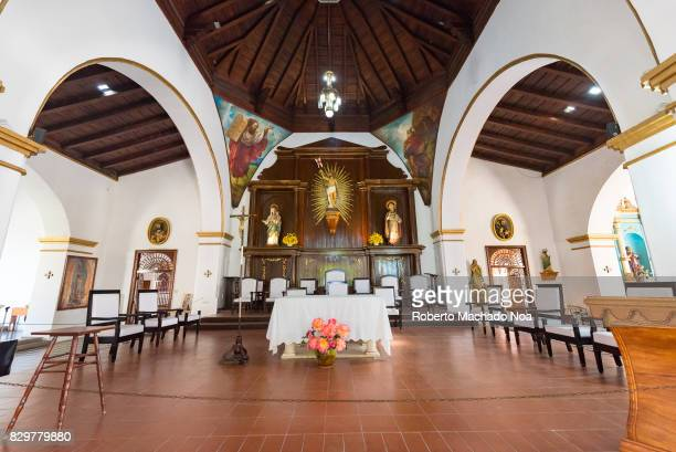 Interior view of the Saint Isidore Catholic Cathedral showing its brown tiled floor wall paintings and rows of chairs for the congregation