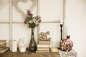 Interior with books, flowers and candles. Bright background with braided white heart