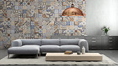 Interior with large blue vibrant sofa with coffee table, large pendant light above, tiles on the wall, with shelf and flowers, carpet. concrete wall, designer template. horizontal composition