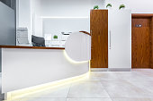 White interior with reception desk and wooden door