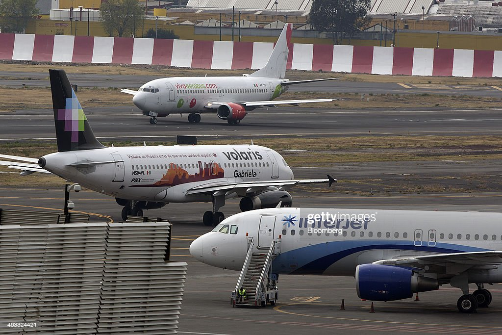 Interjet and Volaris airplanes sit parked on the tarmac while a Grupo Viva Aerobus SAB airplane prepares to take off at Benito Juarez International Airport (AICM) in Mexico City, Mexico, on Thursday, Jan. 16, 2014. Grupo Viva Aerobus SAB filed for what would be Mexico's second initial public offering of shares by an airline since September as passenger traffic sets annual records. Interjet, Mexico's second-biggest carrier in 2012, may sell shares this year, Executive President Miguel Aleman Magnani said in November. Photographer: Susana Gonzalez/Bloomberg via Getty Images