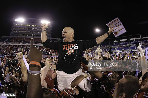 Interm head coach Nick Holt of the Western Kentucky Hilltoppers is lifted onto his players' shoulders following the game against the Memphis Tigers...