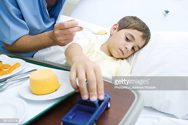 Intern feeding boy in hospital bed