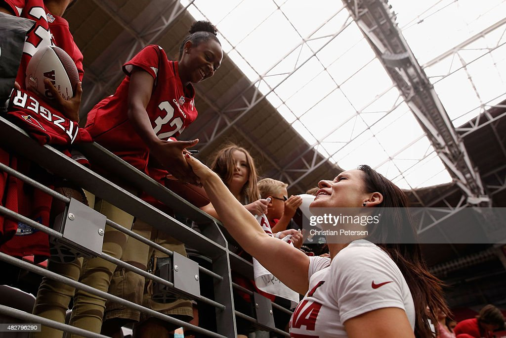 Intern linebacker coach Jen Welter of the Arizona Cardinals greets a young girl following the team training camp at University of Phoenix Stadium on August 2, 2015 in Glendale, Arizona.