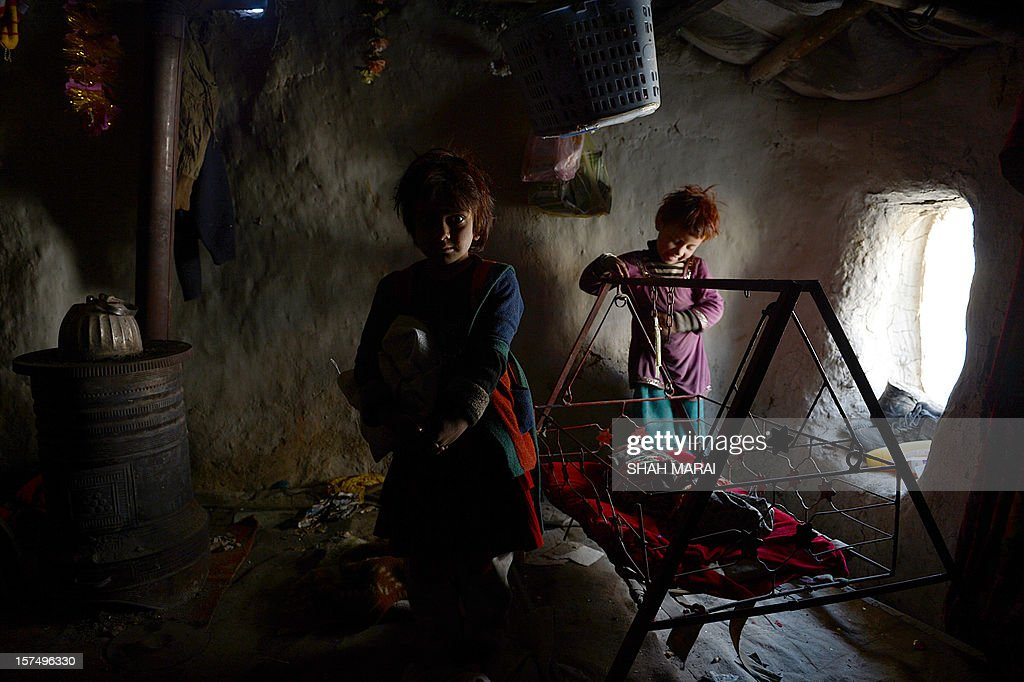 Internally displaced Afghan children play inside a mud shelter at a makeshift camp as winter approaches in Kabul on December 4, 2012. The country has nearly half a million displaced people, many living in primitive camps where the cold weather will mean uncertainty for some. AFP PHOTO/SHAH Marai