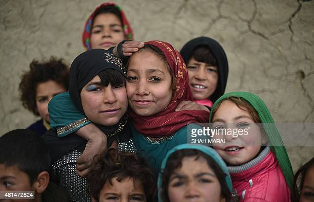 Internally displaced Afghan children pose for a photograph as their parents collect food relief aid from the World Food Programme in Kabul on January...