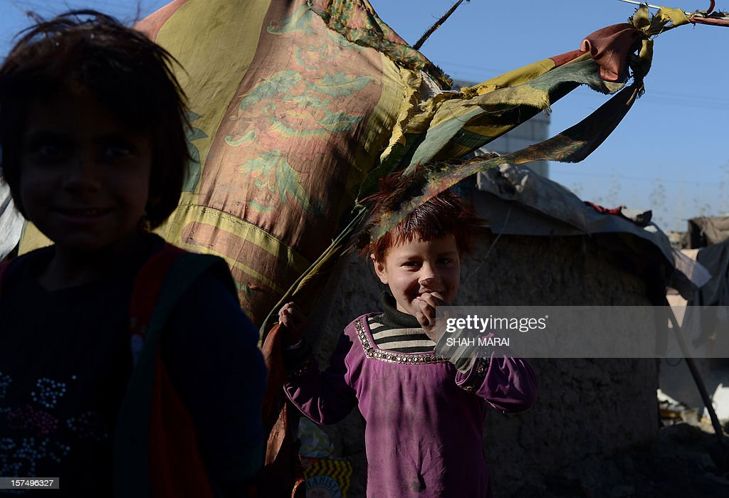 Internally displaced Afghan children stand outside their mud shelters in a makeshift camp as winter approaches in Kabul on December 4, 2012. The country has nearly half a million displaced people, many living in primitive camps where the cold weather will mean uncertainty for some. AFP PHOTO/SHAH Marai