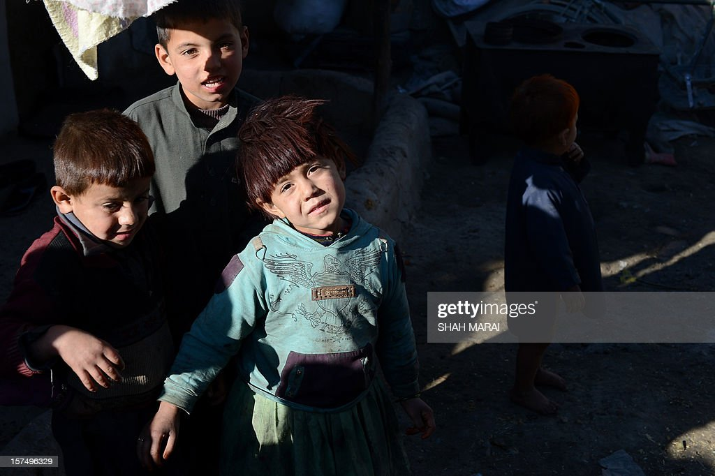 Internally displaced Afghan children stand outside their mud shelters at a makeshift camp as winter approaches in Kabul on December 4, 2012. The country has nearly half a million displaced people, many living in primitive camps where the cold weather will mean uncertainty for some. AFP PHOTO/SHAH Marai