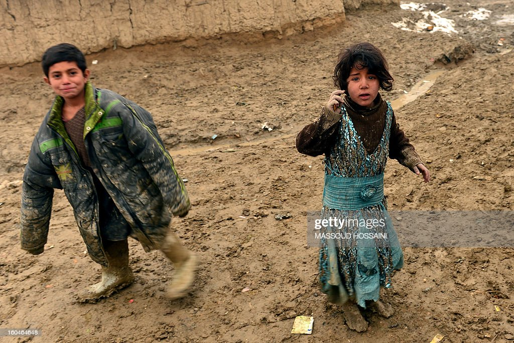 Internally displaced Afghan children wait for donations at Nassaji Camp, east of Kabul, on February 1, 2013. With an ongoing Taliban-led insurgency plaguing the poverty-stricken country, Afghanistan's internally displaced population has reached half a million according to the UN refugee agency, though the actual number is likely to be much higher. AFP PHOTO/Massoud HOSSAINI