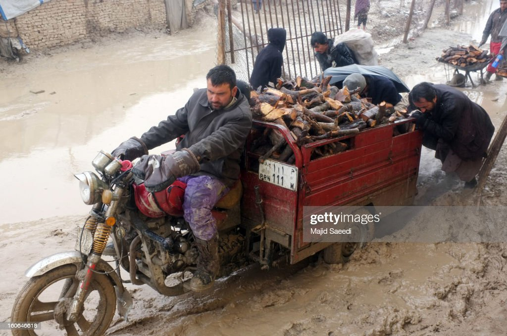 A internally displaced Afghans transport firewood, donated by Danish Refugee Council (DRC), through heavy reain and thick mud on a motorcycle-drawn trailer, at Chamand babrak Camp, on February 3, 2013 in Kabul, Afghanistan. According to the UN refugee agency, Afghanistan's internally displaced population has reached half a million, although the actual figure is believed to be much higher.