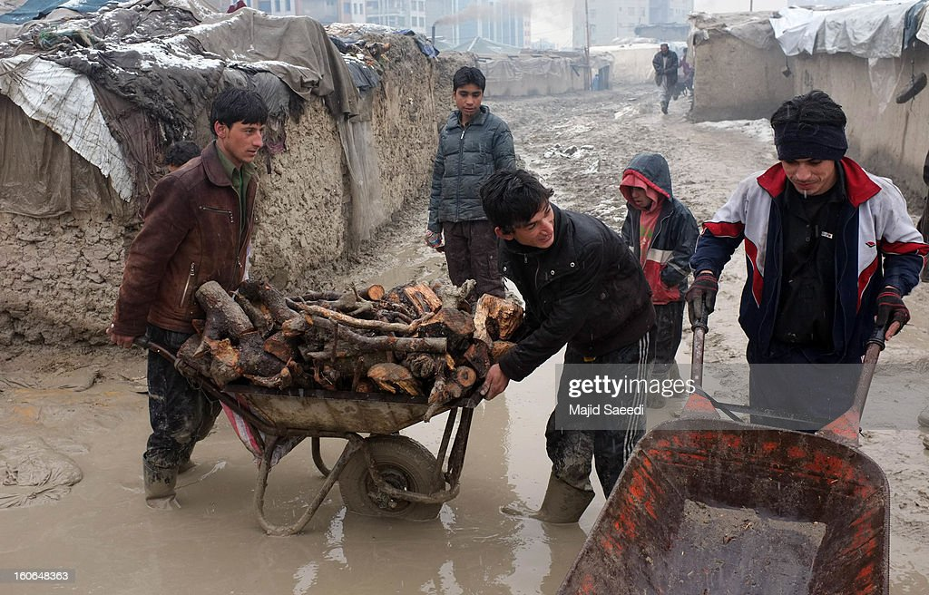 A internally displaced Afghans transport firewood, donated by Danish Refugee Council (DRC), through heavy reain and thick mud, at Chamand babrak Camp, on February 3, 2013 in Kabul, Afghanistan. According to the UN refugee agency, Afghanistan's internally displaced population has reached half a million, although the actual figure is believed to be much higher.