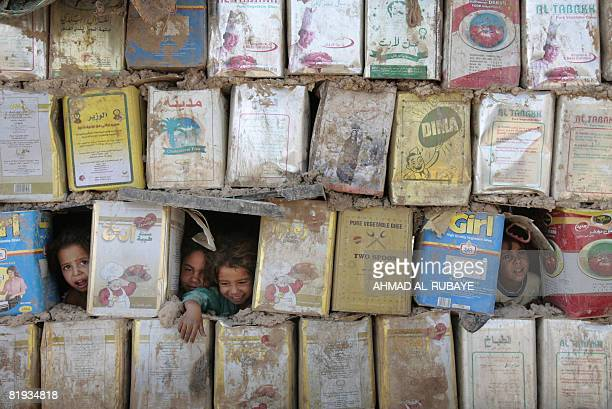 Internally displaced Iraqi Shiite children peek out from the holes of a hut made from mud and cooking oil cans at a squatter settlement in southern...