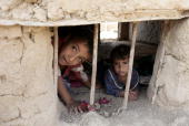Internally displaced Iraqi Shiite children play inside a mud hut at a squatter settlement in southern Baghdad on July 12 2008 The number of...