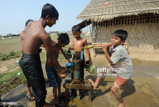 Internally displaced Muslims boys draw water from a public well at a camp on the outskirts of Sittwe in the western Myanmar state of Rakhine on March...